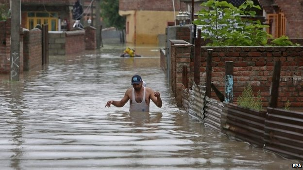 A Kashmiri man wades through flood water in the outskirts of Srinagar, the summer capital of Indian Kashmir on 04 September 2014.