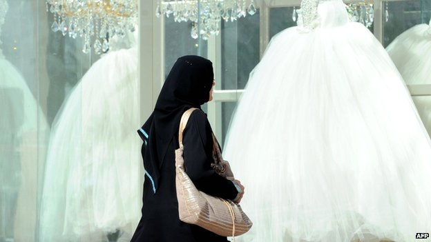 Woman walks past wedding dresses in Saudi shop