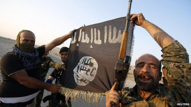 Iraqi Shia militiamen with an IS flag captured as they broke a siege in the Iraqi town of Amerli, 1 Sept