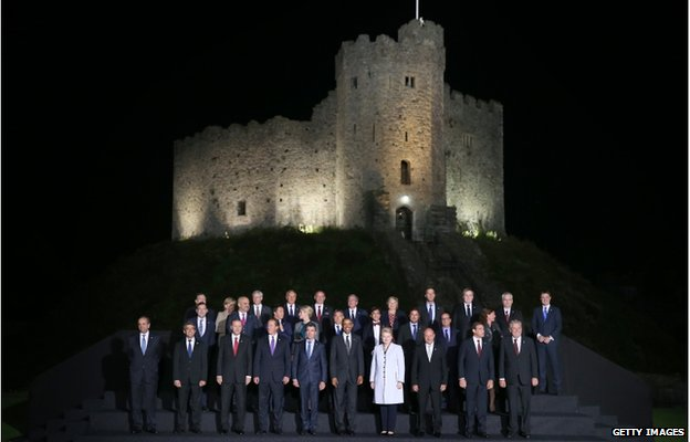 World leaders gathered at night for a photograph outside Cardiff Castle, which is lit up in the background