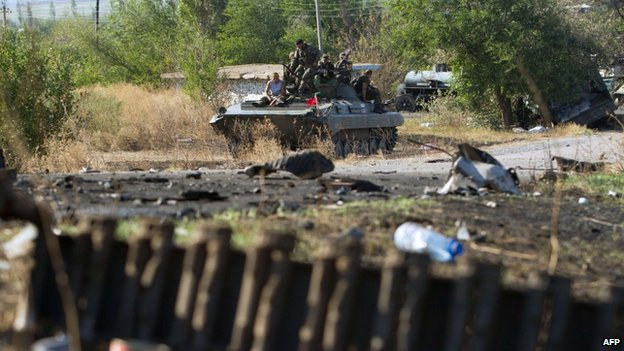 Pro-Russian separatists sit on top an armoured personnel carrier near a destroyed tank on a road in the village of Novokaterinovka, some 50km southeast of Donetsk