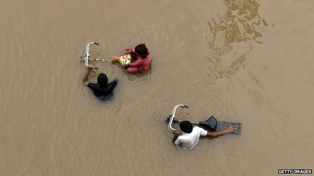 Pakistani residents wade through floodwaters following heavy rain in Lahore on September 4, 2014.