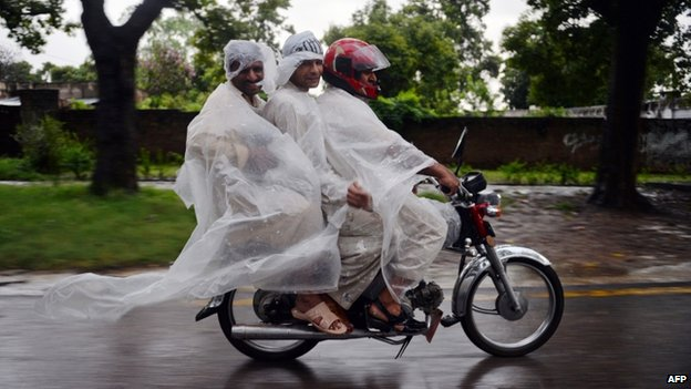 Men in Islamabad in ponchos amid heavy rain - 4 September