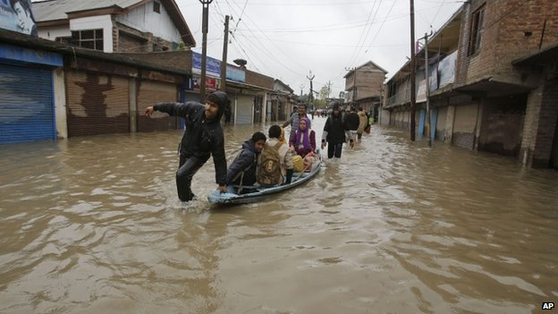 Kashmiris cross a flooded neighbourhood on a boat in Srinagar, India, Thursday, Sept. 4, 2014