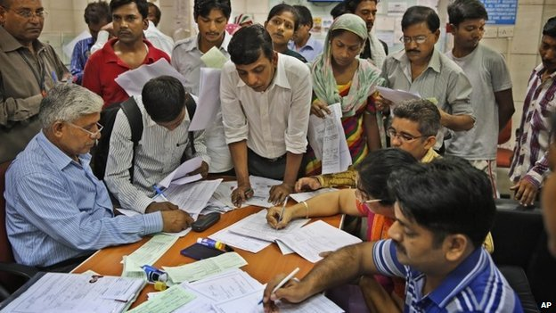Indians gather inside a state-owned bank to open accounts as part of a countrywide campaign to open millions of accounts for the poor in Delhi on Thursday, Aug. 28, 2014.