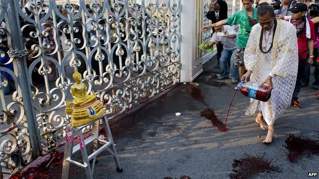 A supporter (C) of deposed Thai Prime Minister Thaksin Shinawatra pours a canister of human blood onto the gates of the Government House in protest in Bangkok on 16 March 2010