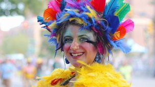 A reveller decked out in brightly coloured feathers