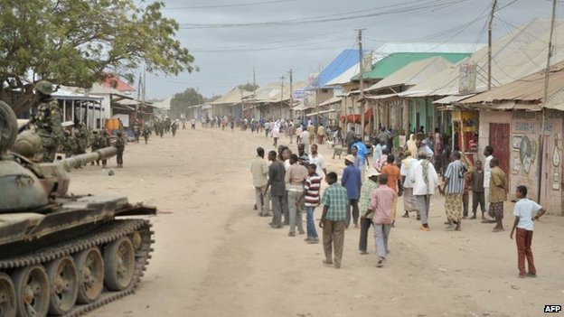 A handout picture taken and released on 31 August 2014 by the African Union-United Nations Information Support Team shows residents of the town of Bulomarer, some 160kms (100 miles) south-west of the capital Mogadishu, in the Lower Shabelle region of Somalia walking in a street after it was liberated by African Union Mission in Somalia troops