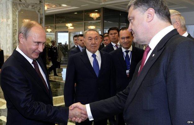 Russian President Vladimir Putin (L) shakes hands with Ukrainian President Petro Poroshenko (R) in Minsk, Belarus, 26 August