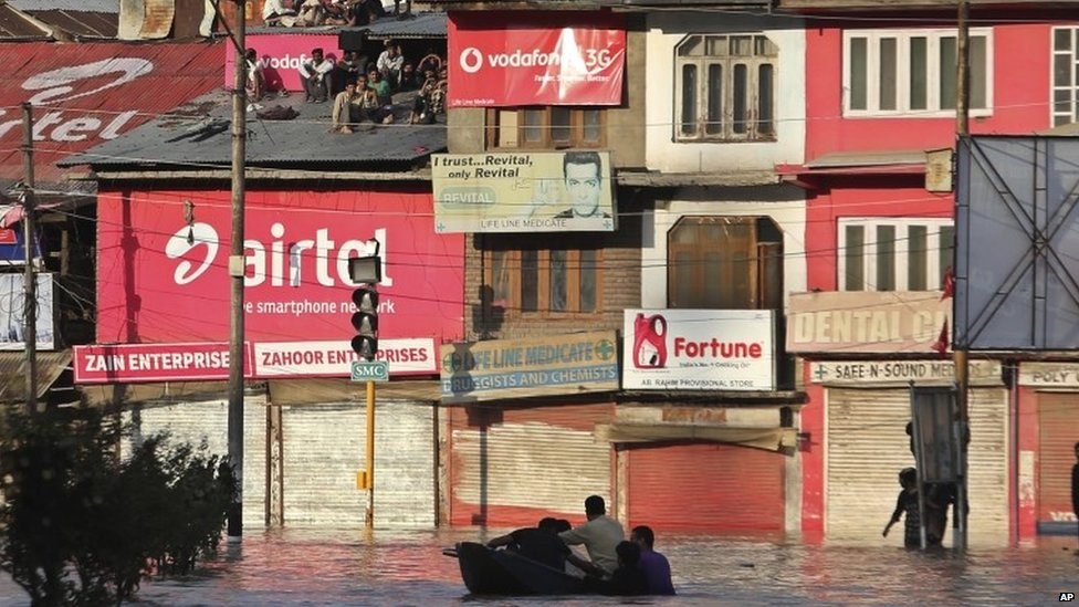 Kashmiri residents watch sitting atop the tin roofs as soldiers evacuate people from their flooded neighbourhood in Srinagar, India, Sept 7 2014