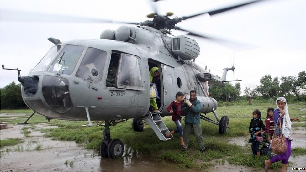 An Indian Air Force personnel helps a flood victim girl to disembark from a MI-17 helicopter after she was evacuated during a rescue operation at a flooded area in Hamirpur Kona in Rajouri district, northwest of Jammu September 6, 2014.