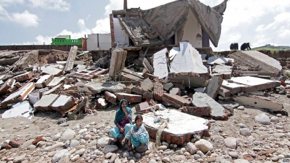 Indian woman along with her child sit outside her destroyed house during flash floods in Jammu, the winter capital of Kashmir, India, 07 September 2014