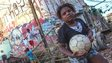 A child holds a football in a Sao Paulo favella