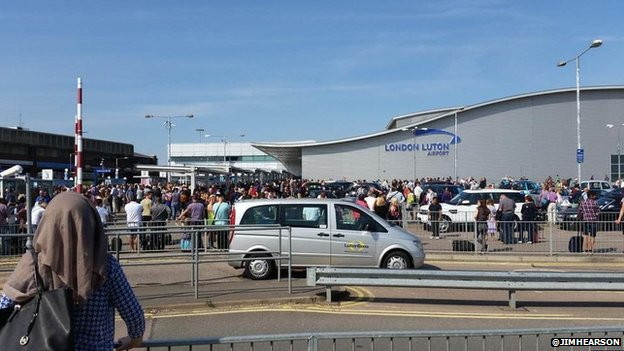 Passengers outside Luton Airport