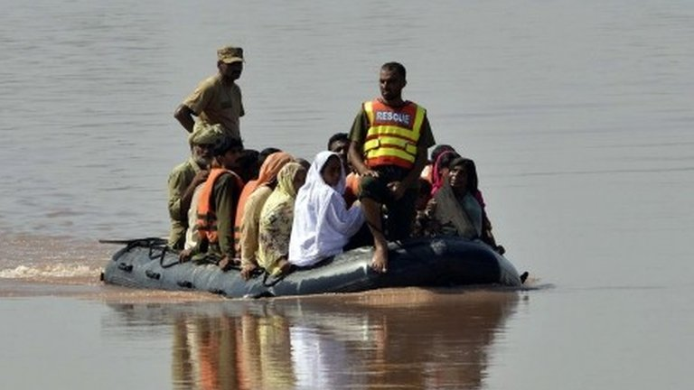 Pakistani soldiers use an inflatable boat to rescue flood-affected residents from a village at Jalalpur Bhattian in the Hafizabad district in Punjab province on September 8, 2014
