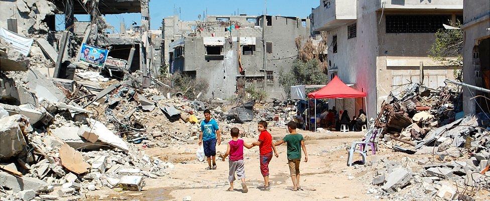 Children walk through the rubble