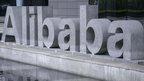 People walking past Alibaba sign