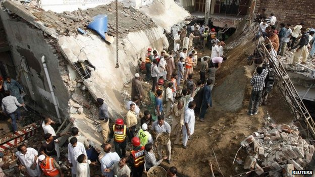 Residents and rescue workers gather at the site of a mosque, after its roof collapsed, in Lahore (9 September 2014)