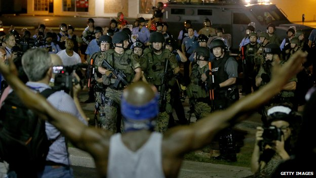 A demonstrator stands in front of police in Ferguson, Missouri, on 19 August, 2014.