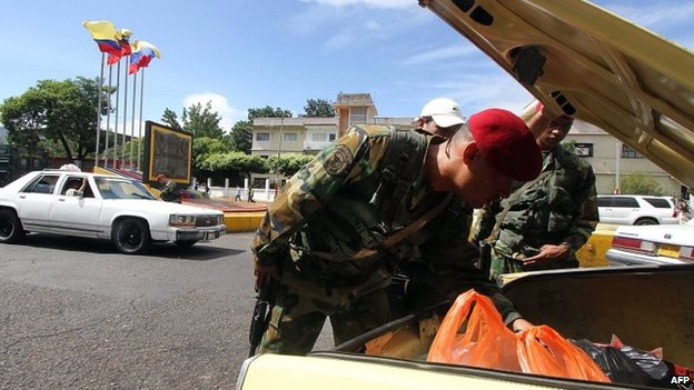 Venezuelan troops search for smuggled goods in a car heading to Colombia in the border city of San Cristobal (20 August 2014)
