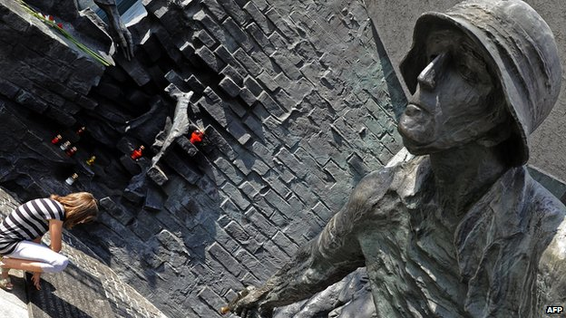 Woman at a Warsaw monument commemorating the Polish who fought German occupation troops during the Warsaw Uprising in World War II