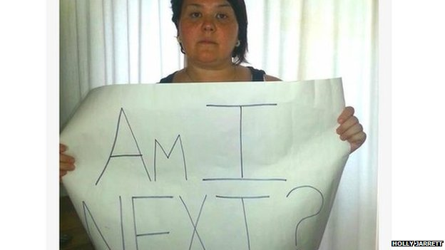 "Woman holds ""Am I next"" sign?"