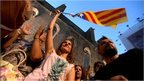 Protesters fly a Catalan flag