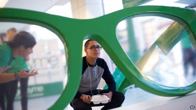 Man looks through a giant pair of glasses