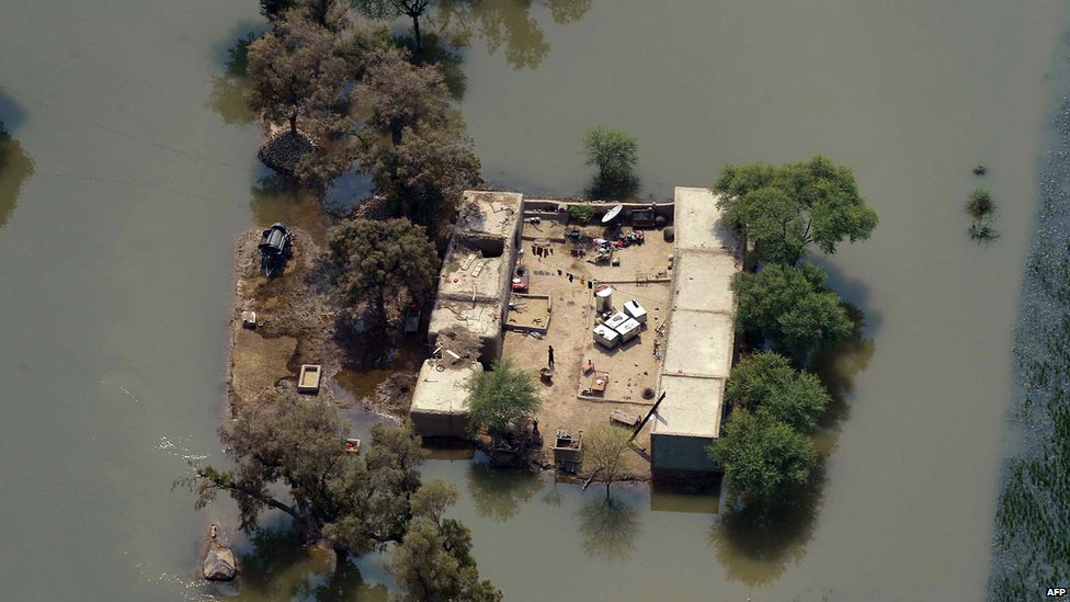 An aerial photograph from a Pakistani army helicopter shows people in a homes surrounded by floodwaters in the area of Peer Kot in Jhang, central Punjab province (11 September 2014)