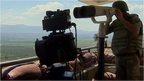 Turkish soldier surveying border through telescope