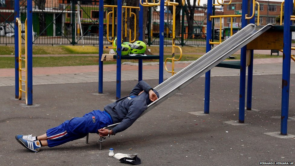 A detainee rests, handcuffed to a slide, at a children's playground in a public park in Bogota, Colombia.
