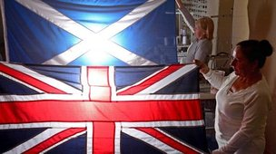 Members of staff at James Stevenson Flags hold a Union Jack and Saltire flag