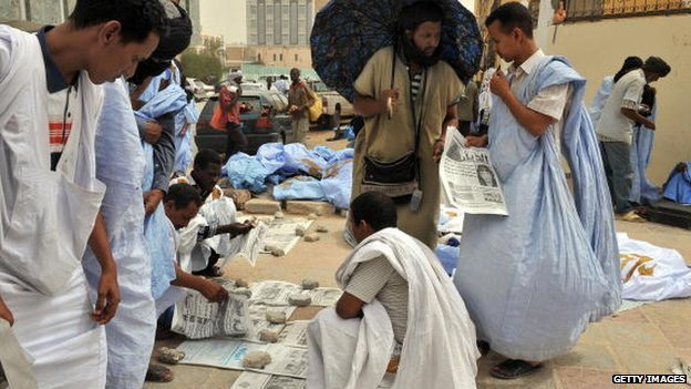 Mauritanians read newspapers on a main street in Nouakchott