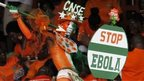 A fan of Ivory coast holds a sign with a message against Ebola during the 2015 African Nations Cup qualifying soccer match between Ivory Coast and Sierra Leone at the Felix Houphouet Boigny stadium in Abidjan, 6 September 2014