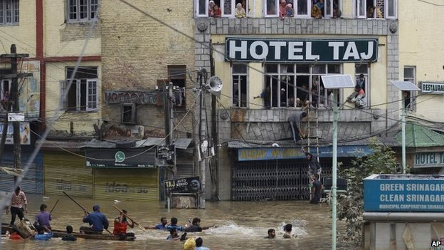 Flood victims watch from the windows of a hotel as Kashmiri volunteers try to get relief material  to them 12 September