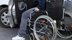 A disabled person getting into their car transferring from their wheelchair