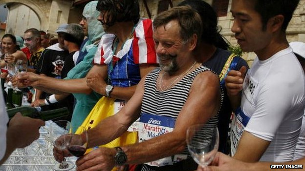 Runners enjoy wine at a chateau during a food and wine break
