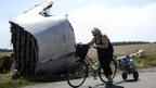 A woman walks with her bicycle near the crash site of the Malaysia Airlines Flight MH17