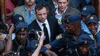 South African Paralympic athlete Oscar Pistorius (C) leaves the High Court in Pretoria on 12 September 2014