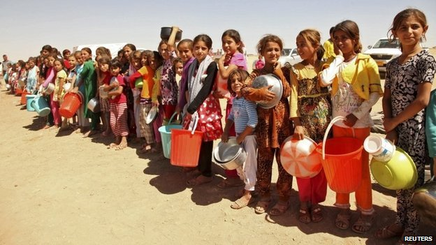 Displaced people from the minority Yazidi sect, fleeing violence in the Iraqi town of Sinjar west of Mosul, line up to receive food at a refugee camp - 13 September 2014