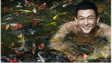 Kenny Yap in  a pool of fish