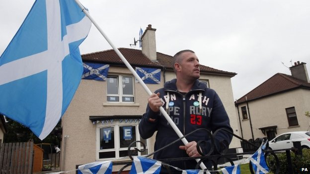 A Scotsman waves a Scottish flag outside his home