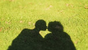 shadow of people kissing on grass