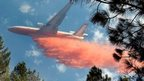 An air tanker drops a load of fire retardant on a wildfire
