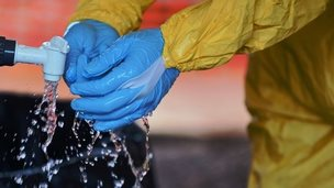 A medical worker in Kailahun, Sierra Leone washes their gloves in chlorine on 15 August 2014.