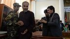 Azizullah (second left), the leader of seven men who gang-raped four women on 23 August, is brought up to testify in court in Kabul on 7 September 2014