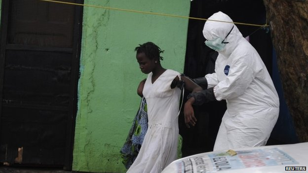 A health worker brings a woman suspected of having contracted the Ebola virus to an ambulance in Monrovia, Liberia (15 September)