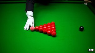 A referee sets up the balls on a snooker table