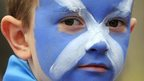 A young boy with his face painted with the Scottish Flag waits for the Team Scotland Commonwealth Games parade in Glasgow, Scotland on August 15, 2014
