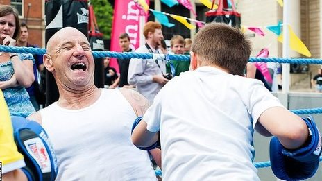 Man having fun in a boxing ring with a young boy